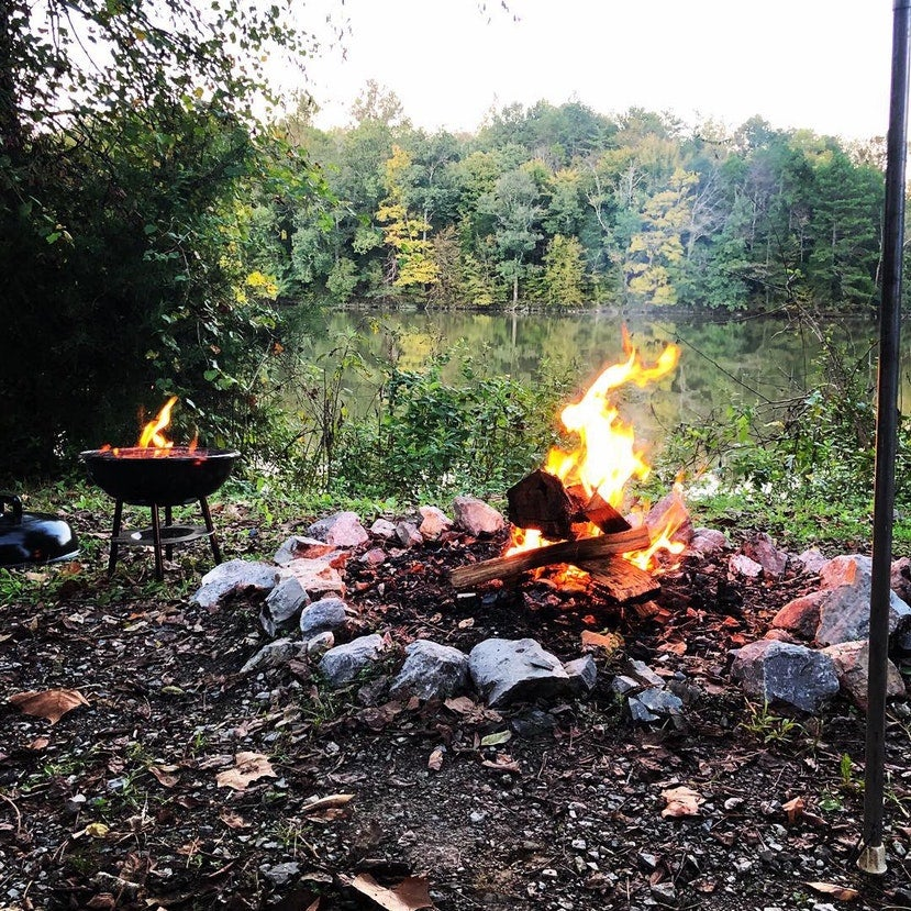 a tailgate grill sits next to an open fire near a lake