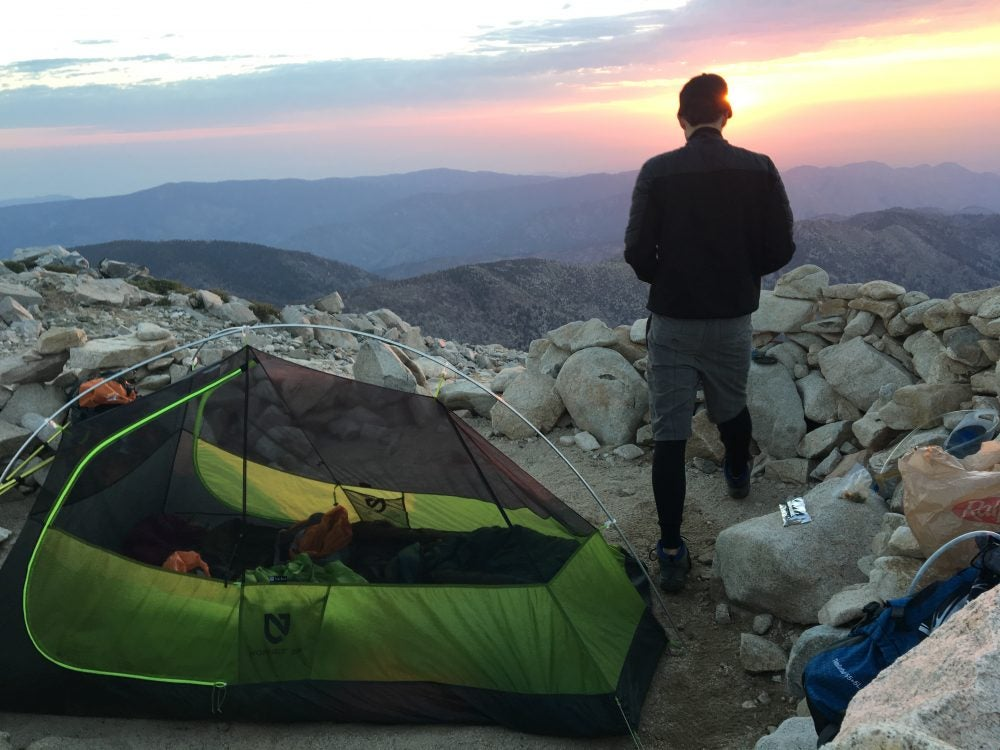 man stands beside green backpacking tent on rocky mountainside as the sun sets in the background