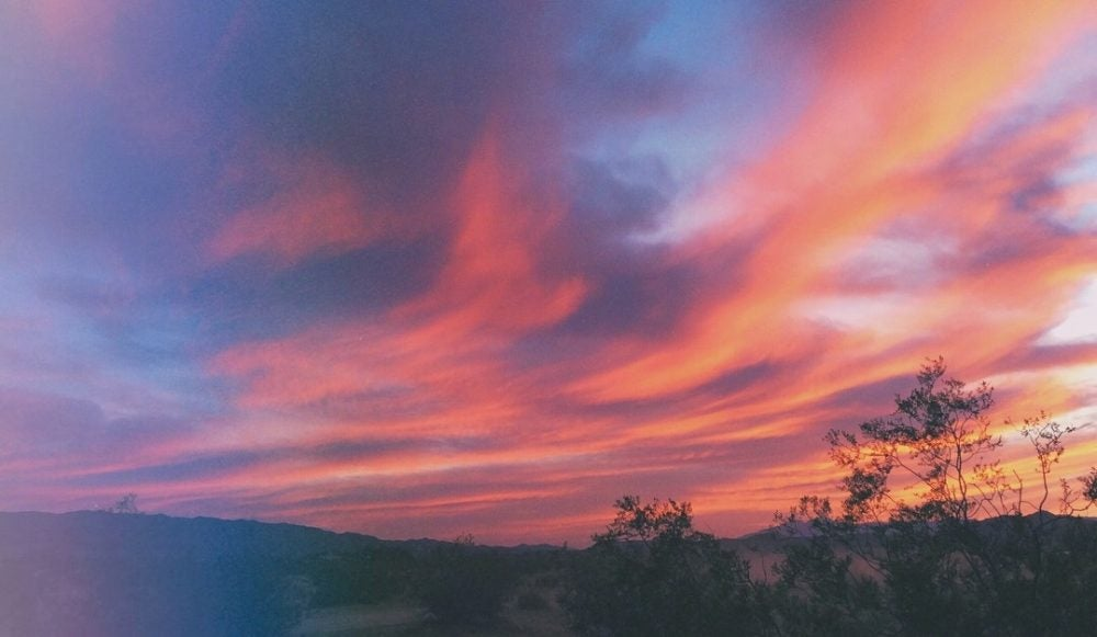 wispy pink and purple clouds cover the sky over palm springs at sunset