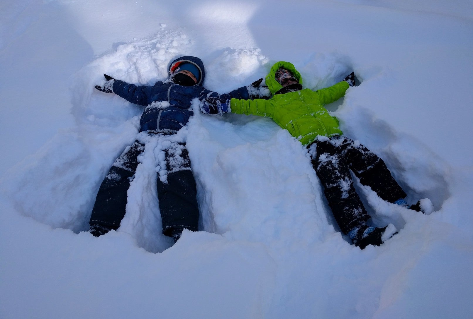 two children in winter gear making snow angels