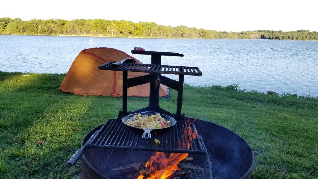 Beautiful scenery including a lake and trees while a lit campfire cooks food on a campfire stove