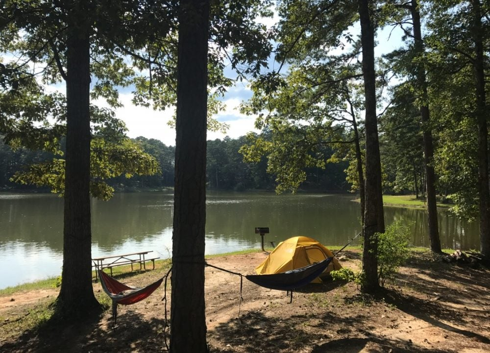 Tent and hammocks along a lake in LeFleur's Bluff State Park