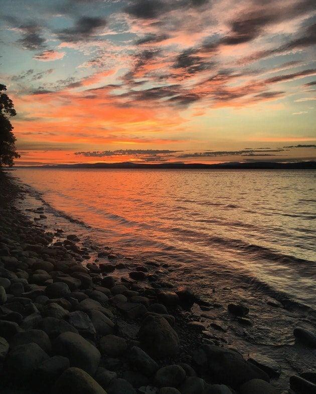 A sunset illuminates a rocky beach of Lake Champlain at Vermont's Grand Isle State Park