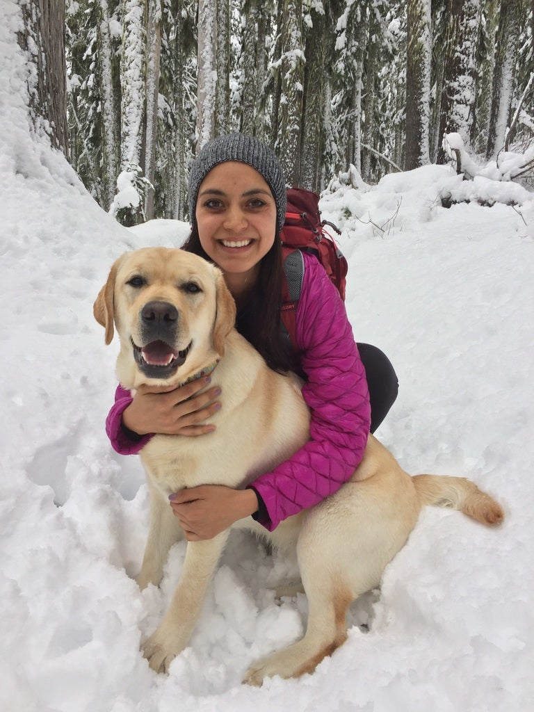female winter camper in purple jacket poses for a photo with her yellow lab in the snowy forest