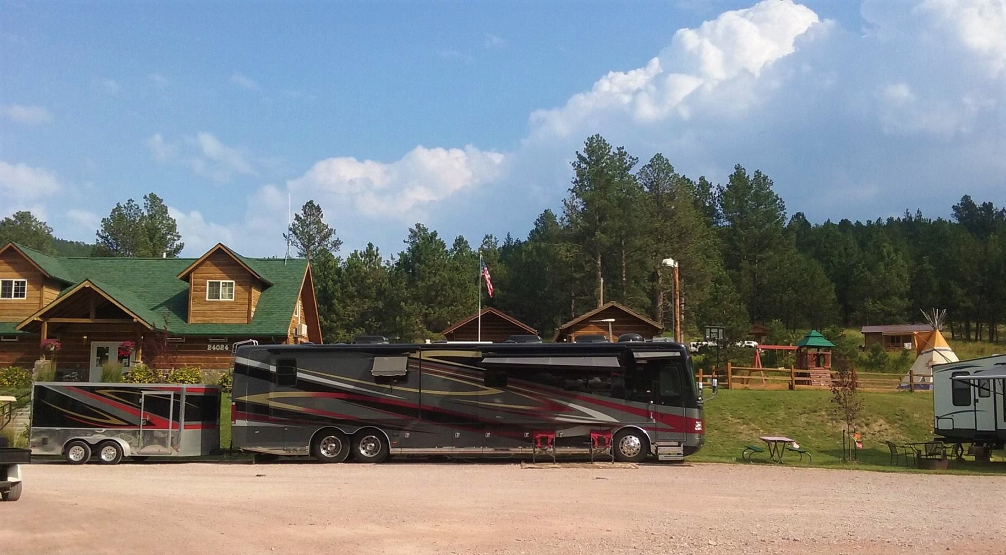 large red, gray, and black rv parked in from of log building at black hills trailside park resort
