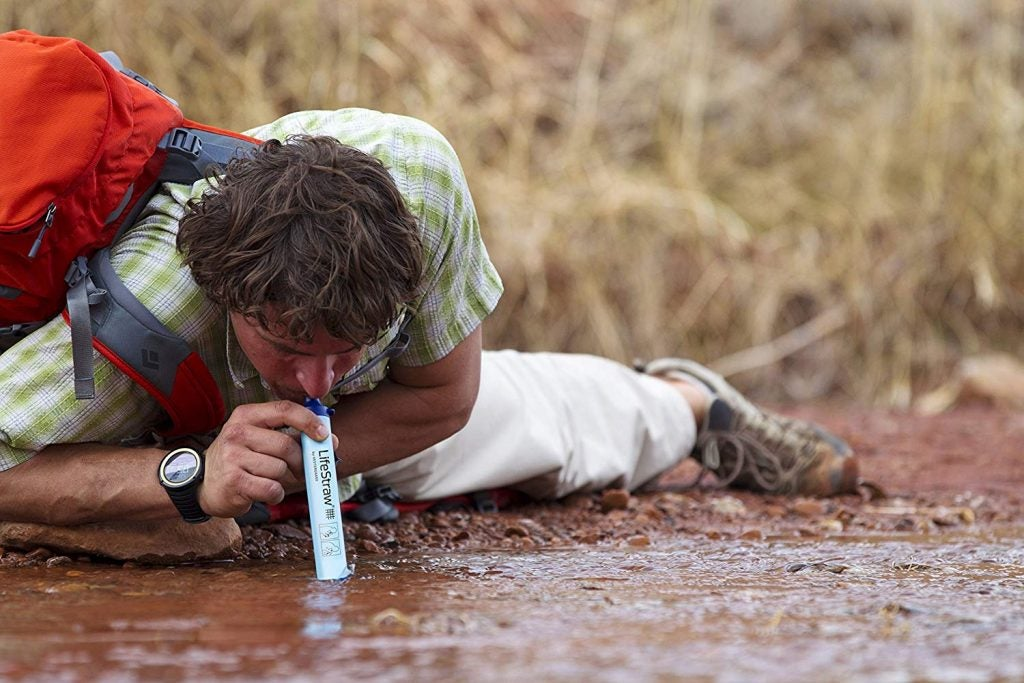 man lying on the ground using lifestraw in a muddy river