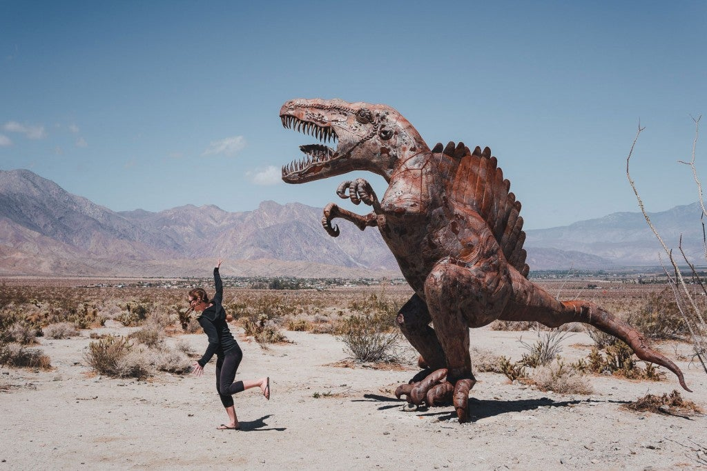 woman poses for photo running away from a dinosaur sculpture in the anza-borrego desert