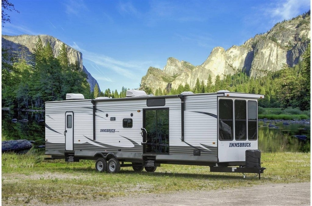 a destination trailer set up in a valley campsite with mountains in the background