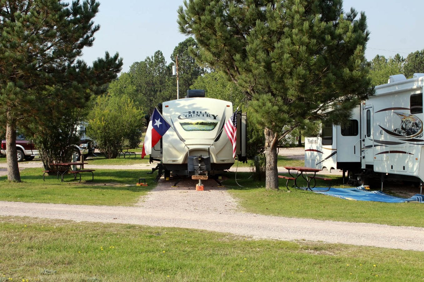 camper trailer backed into campsite between pine trees with a texas and american flag on each side