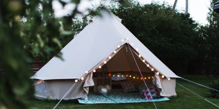 canvas glamping tent adorned with string lights and blue carpet