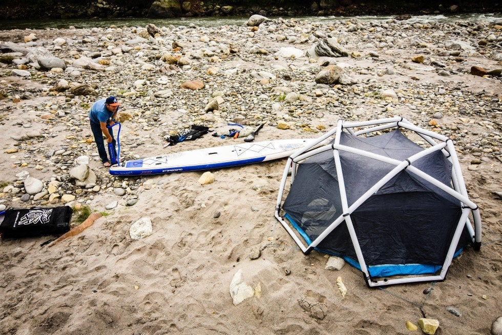 surfer prepares his board beside a heimplanet inflatable tent on a rocky beach