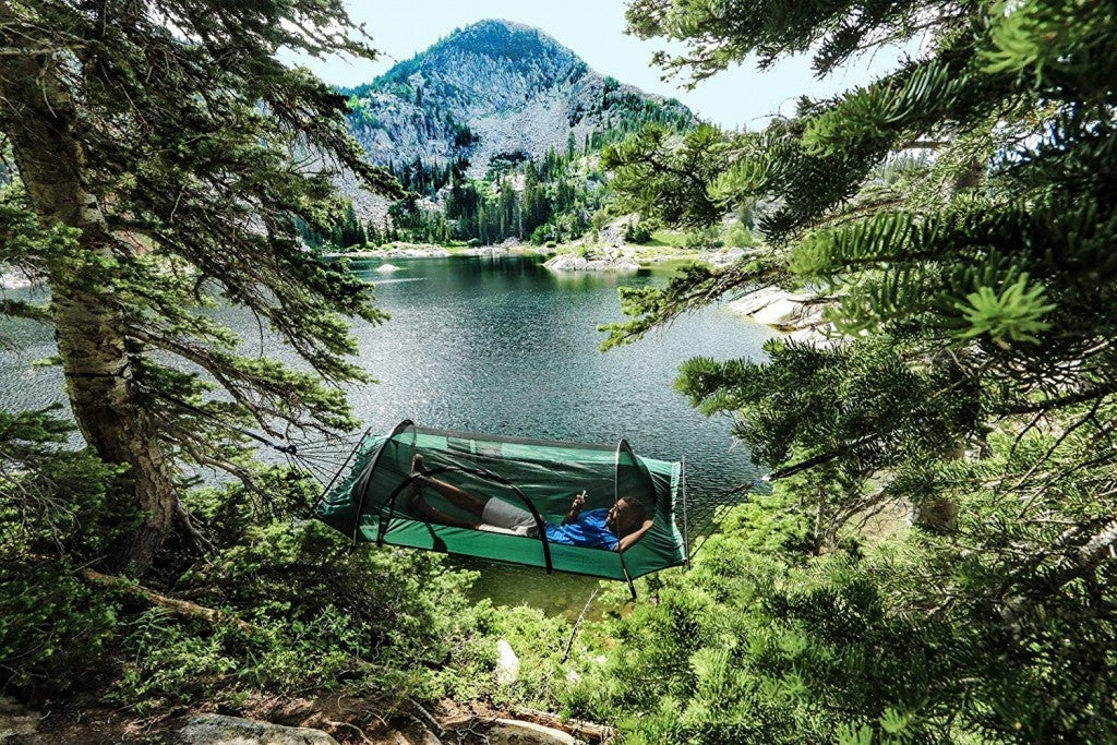 man reclines in a covered camping hammock suspended near alpine lake