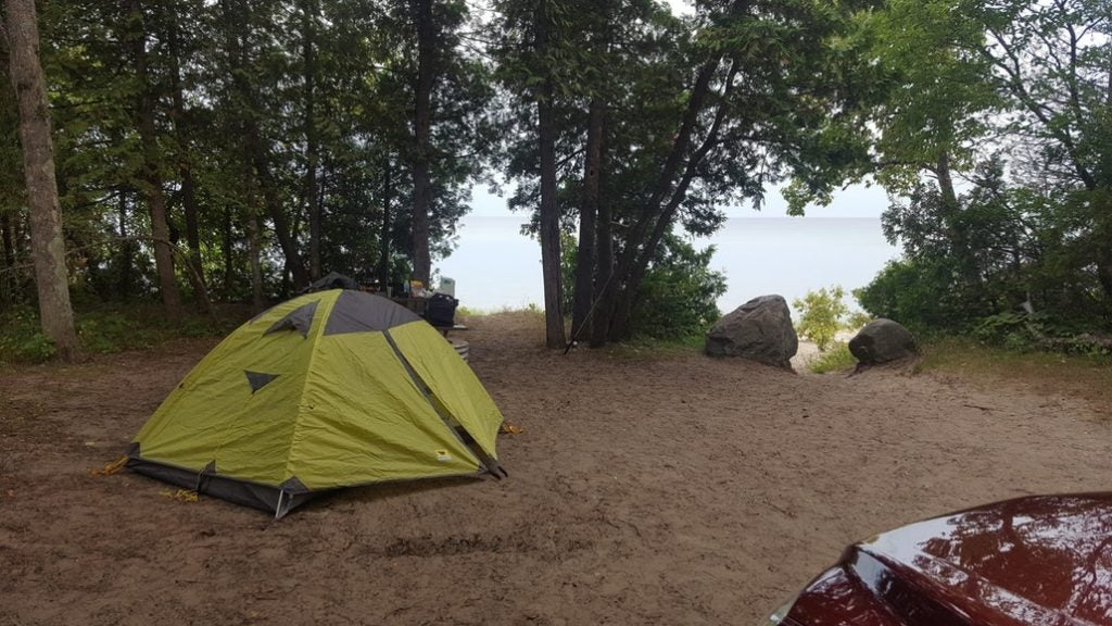 a green tent surrounded by trees with lake access nearby