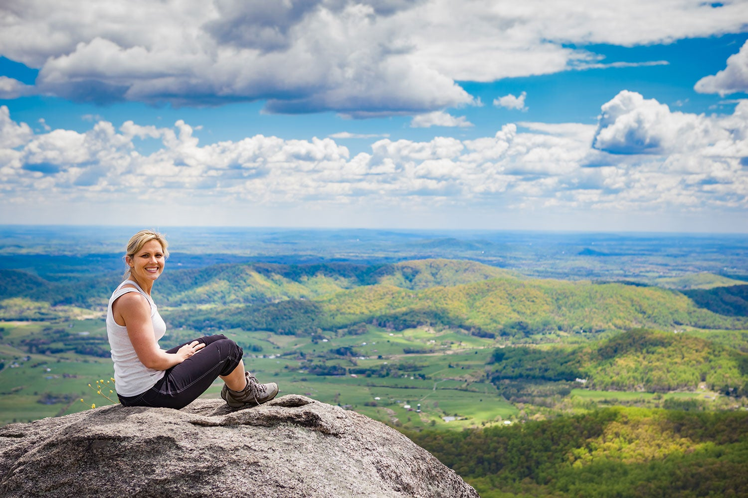 female hiker sitting for a photo atop old rag mountain with a panoramic view in the background