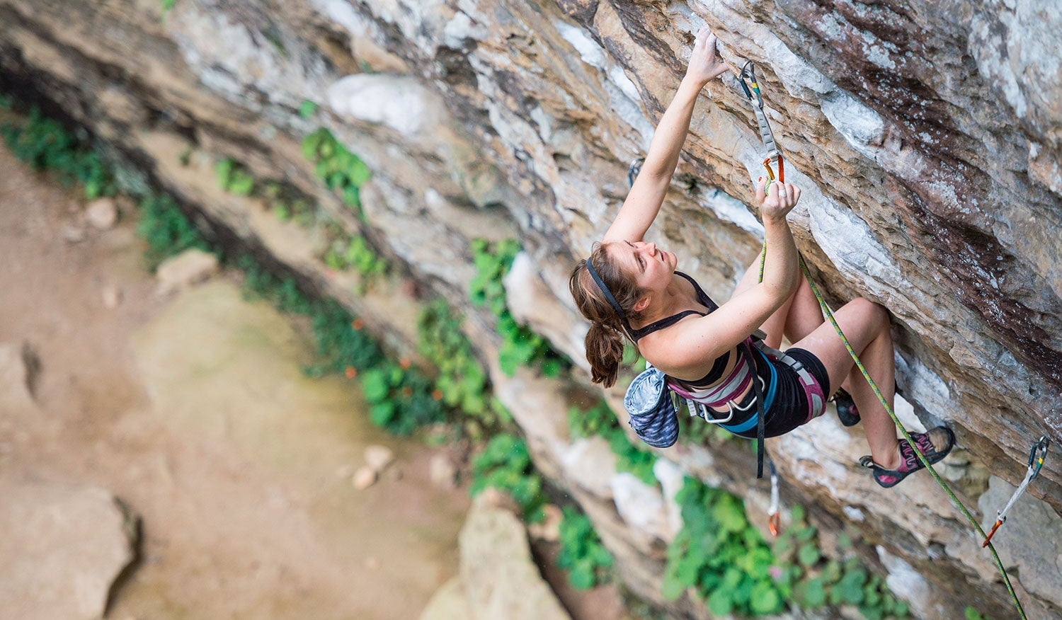 climber makes her way up an outdoor rock wall in the daytime