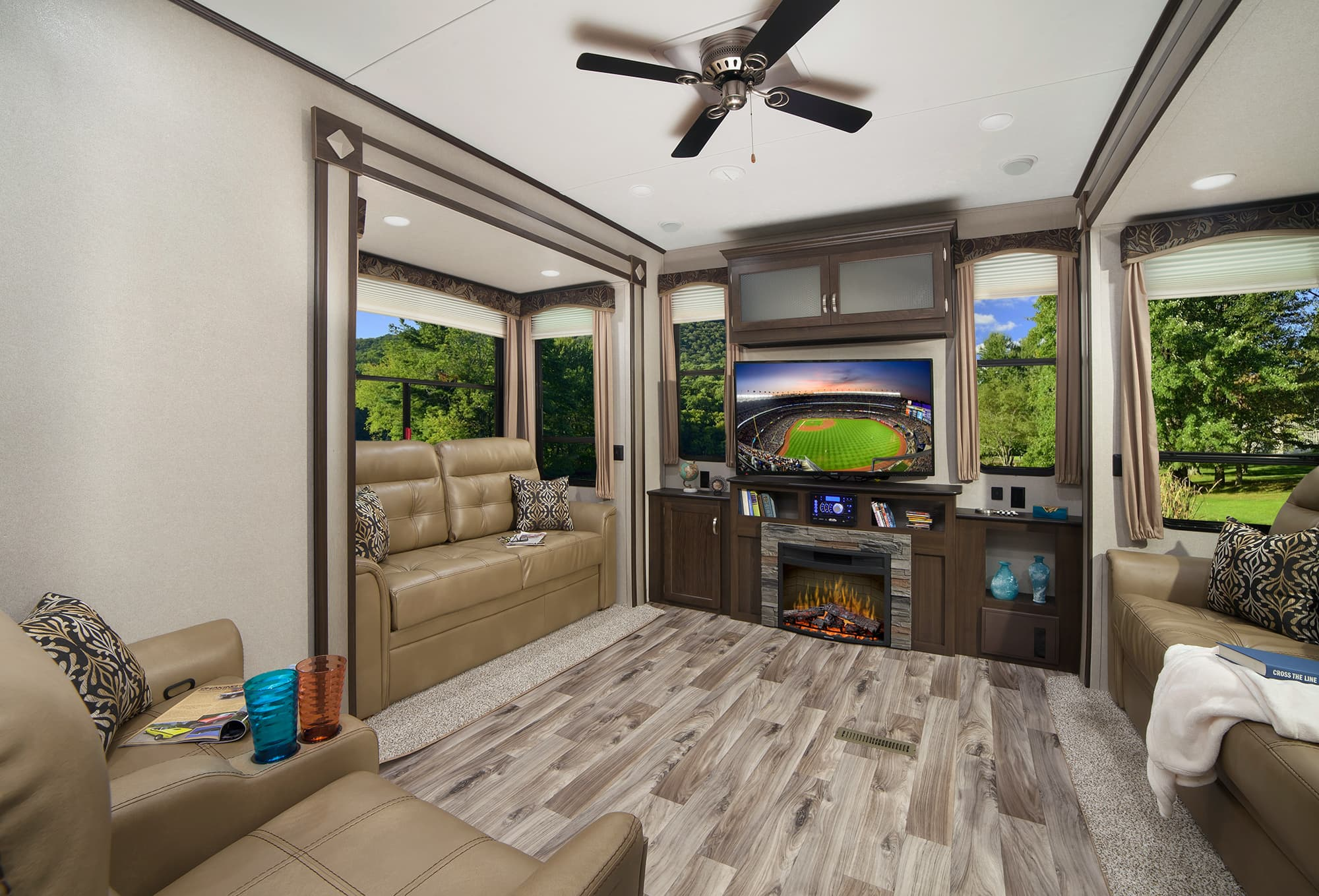 interior of a destination trailer with couches wood floor fireplace and tv