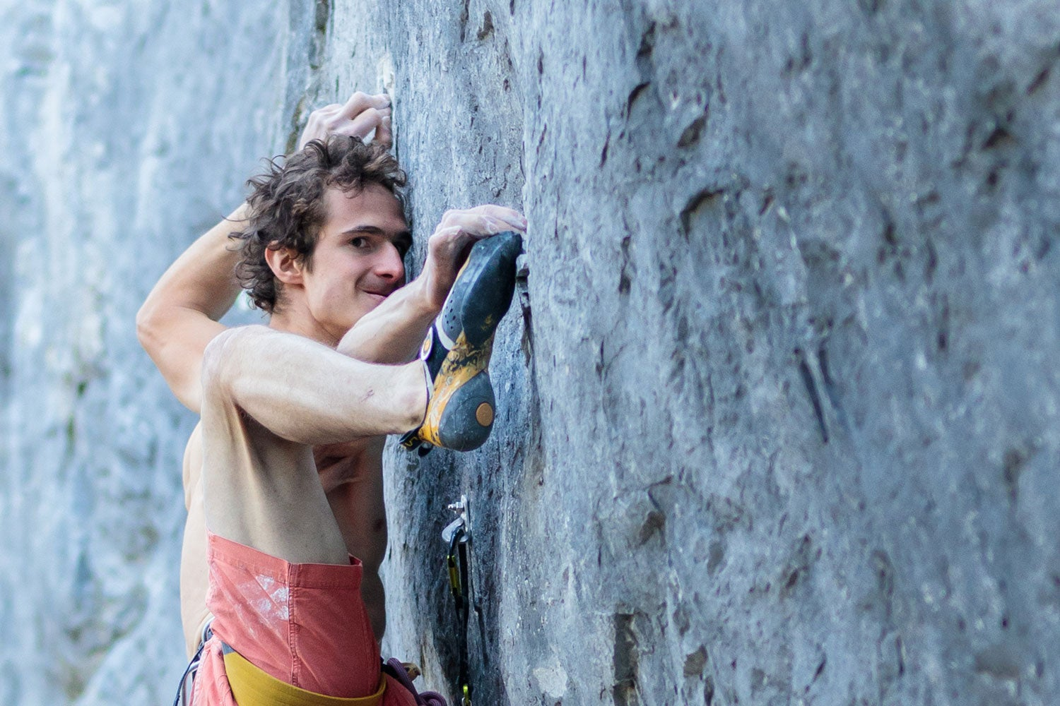A climber clings to a vertical wall, grimacing as he matches he foot to his hand hold.