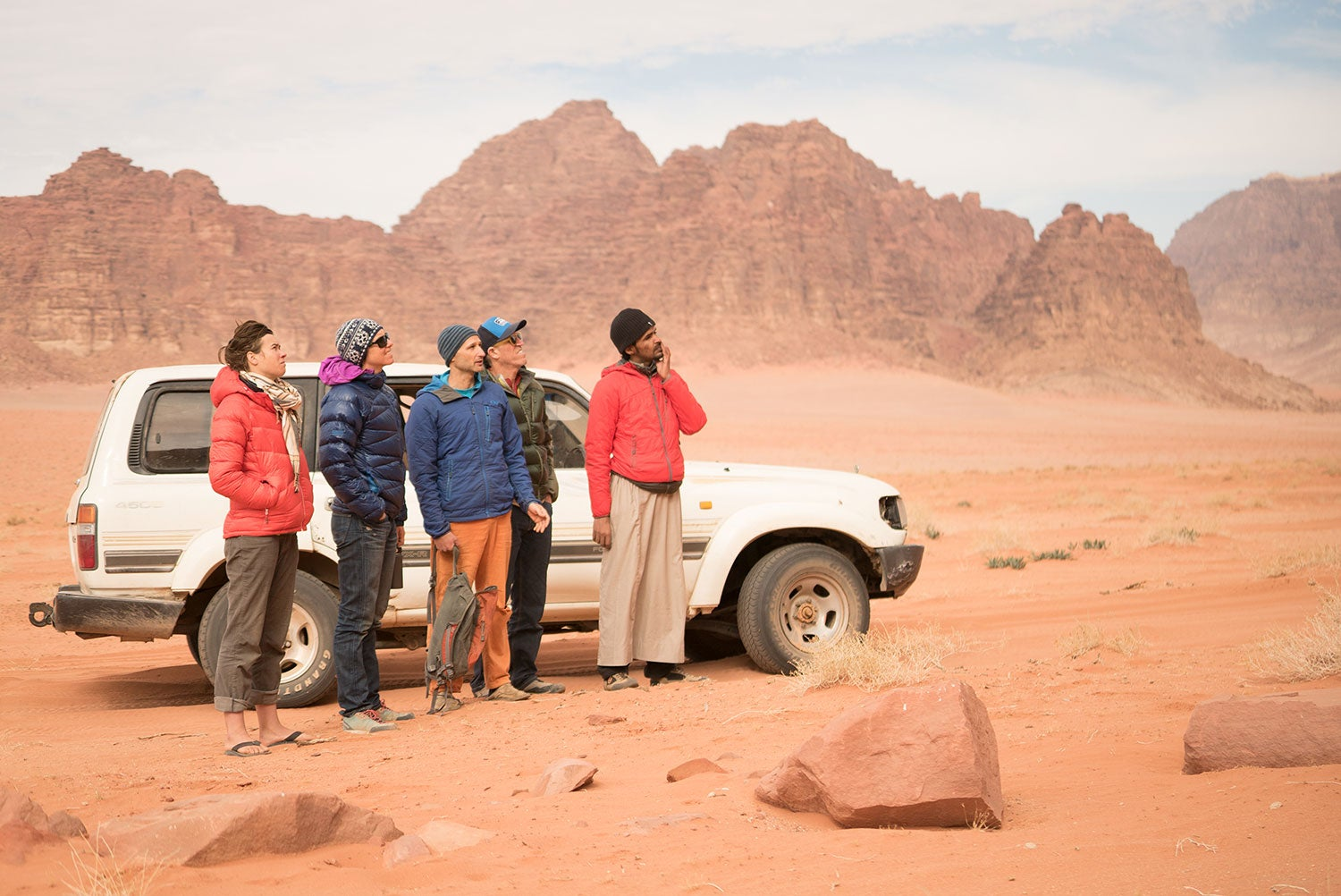 Five people standing in a red desert landscape next to a white SUV.