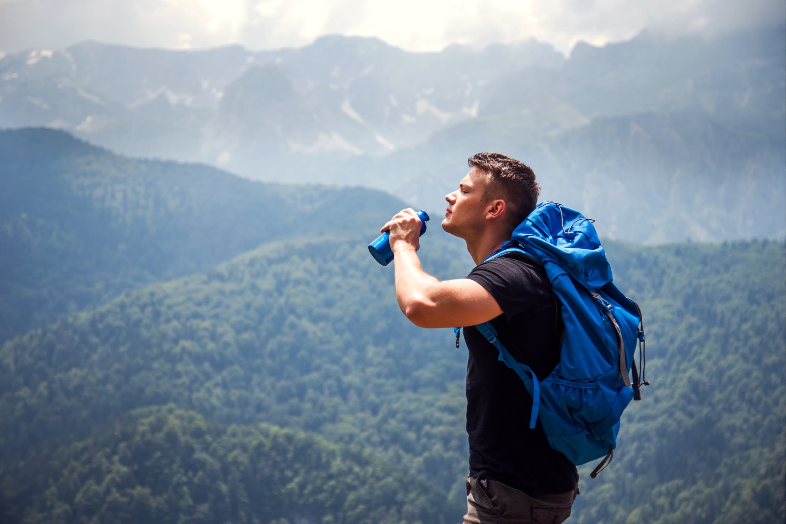 hiker drinking from a bottle of water at the top of a mountain with rolling hills in the background