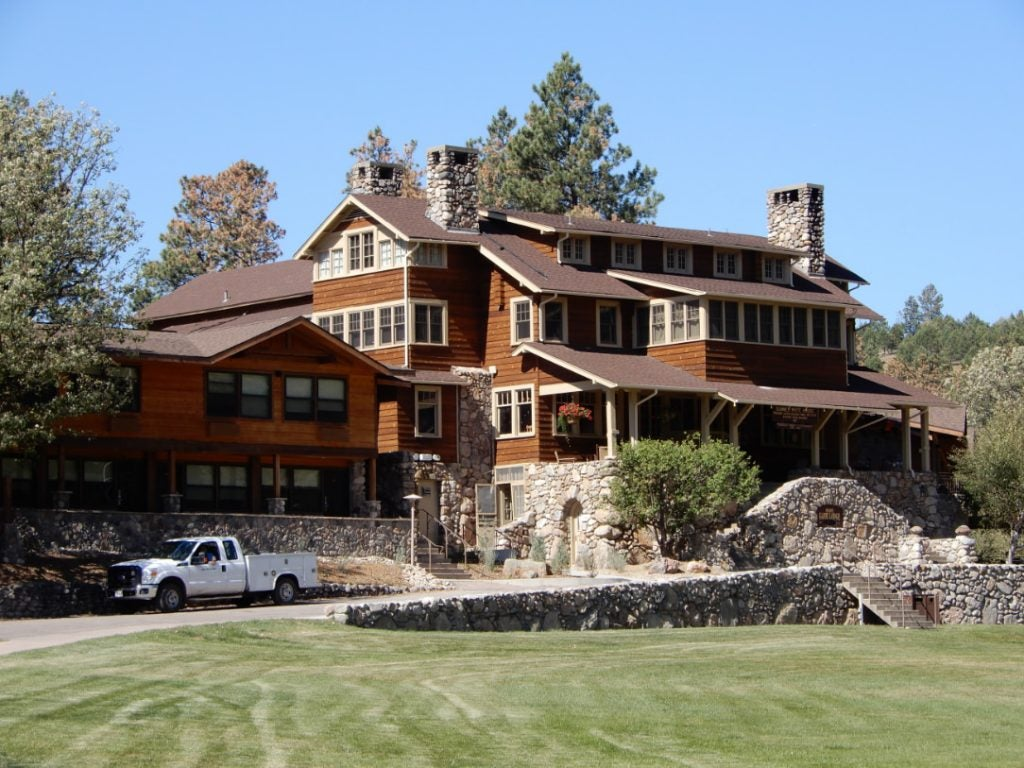 a manicured front lawn and the towering state game lodge in custer state park