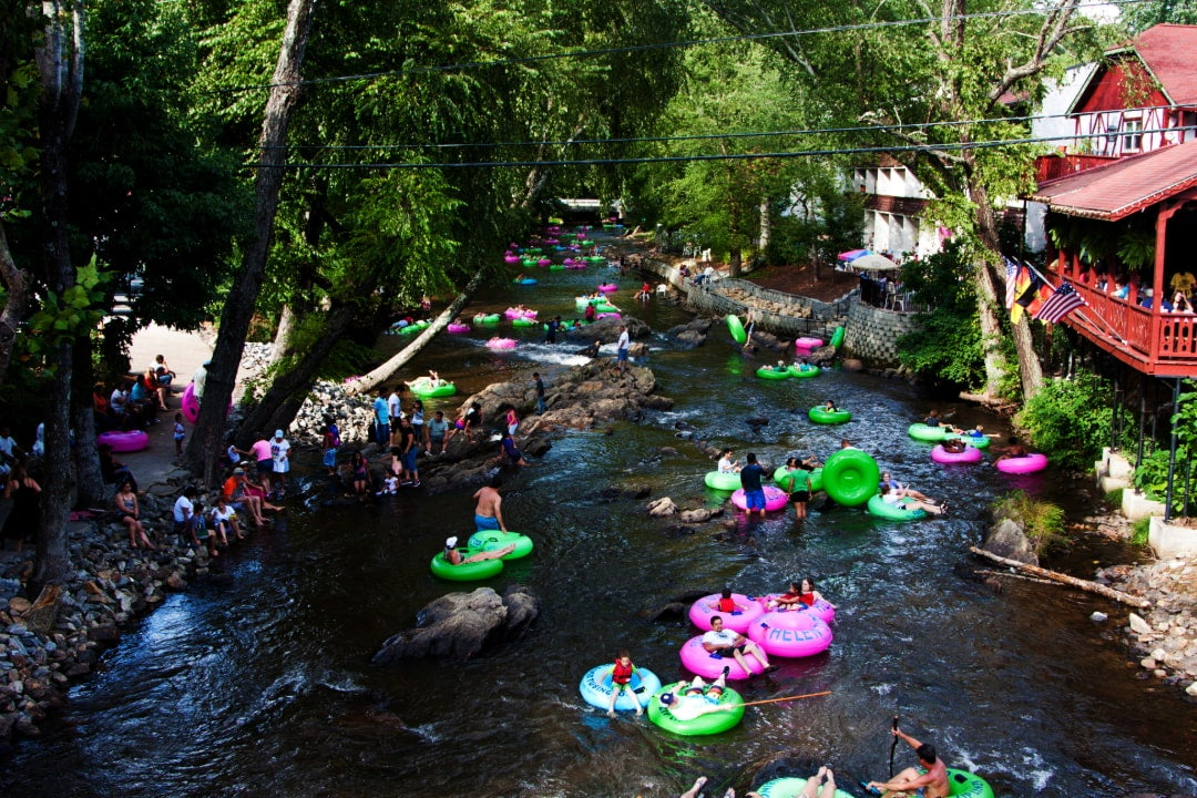 people in inner tubes float down a river