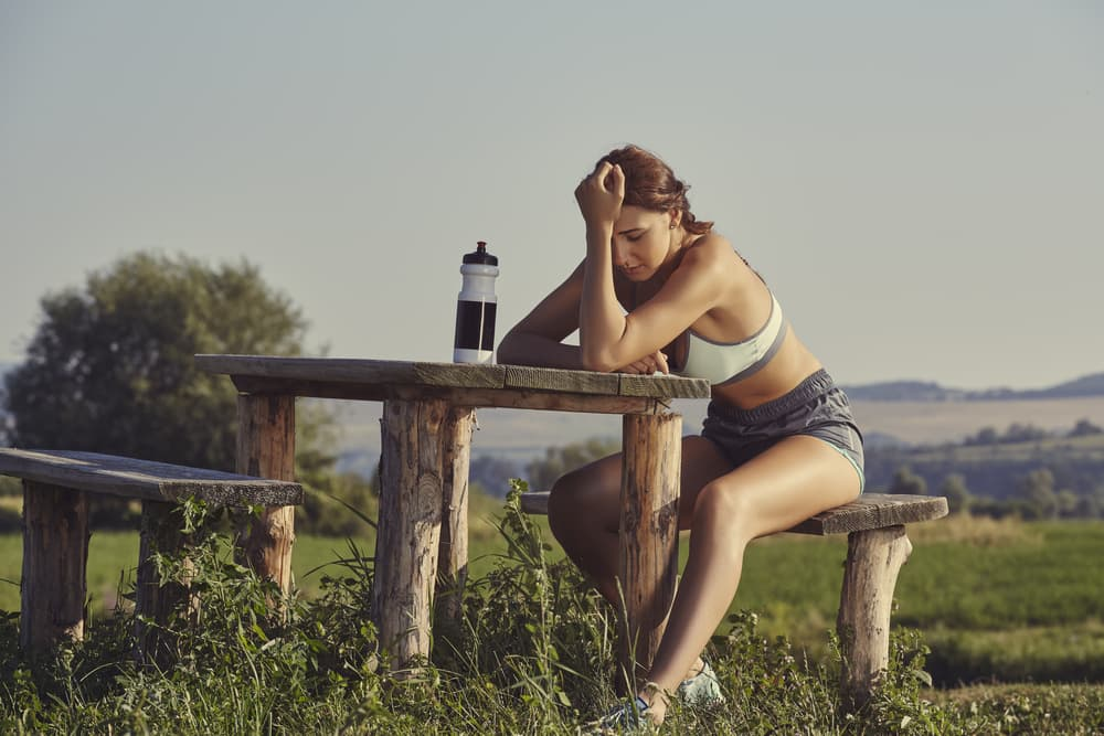 exhausted female runner resting on a rustic wooden bench with hand on head and water bottle at her side