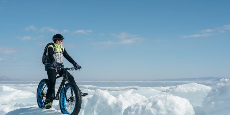 cyclist on a fat tire bike traverses large snow mounds on a clear winter day