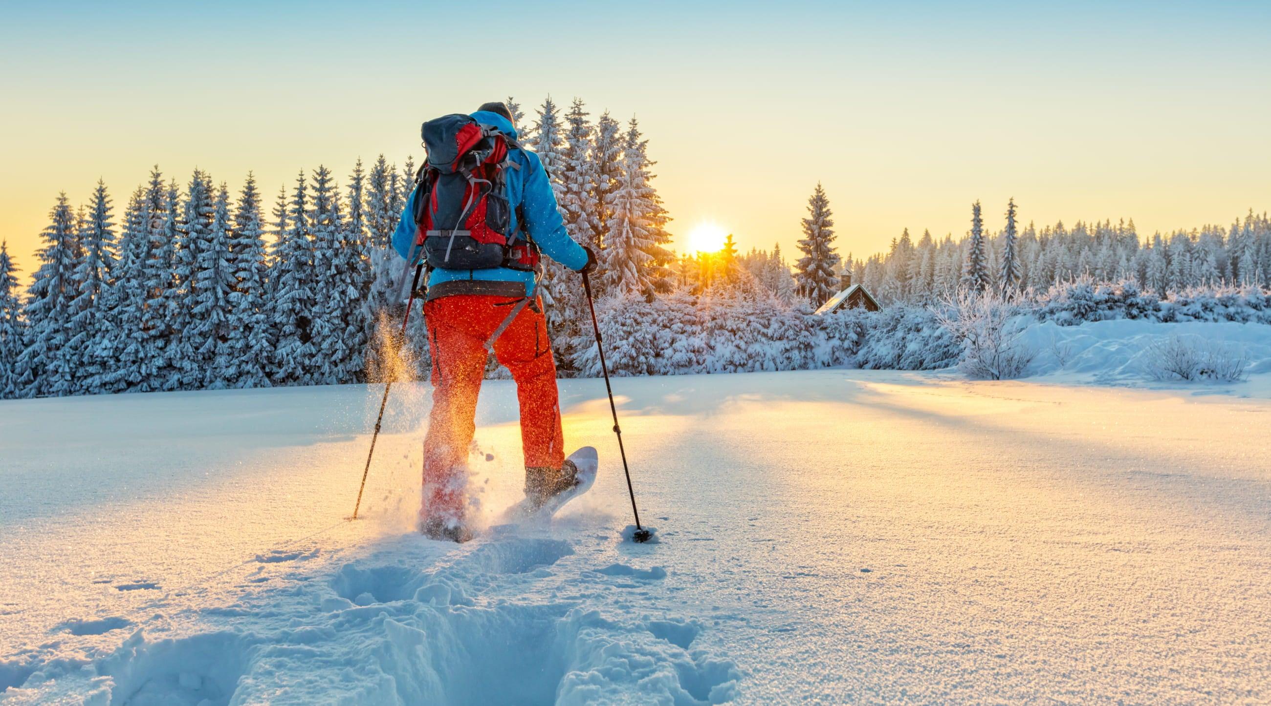 snowshoer in red pants and blue coat walking across snowfield towards sun and treeline