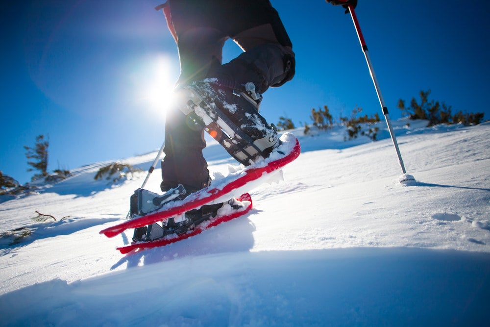 ground view of man in snowshoes with trekking poles is the snow in the mountains.