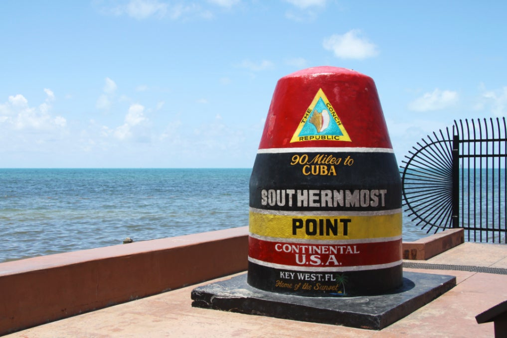 a concrete buoy in front of the gulf of mexico indicating the southernmost part of the U.S.