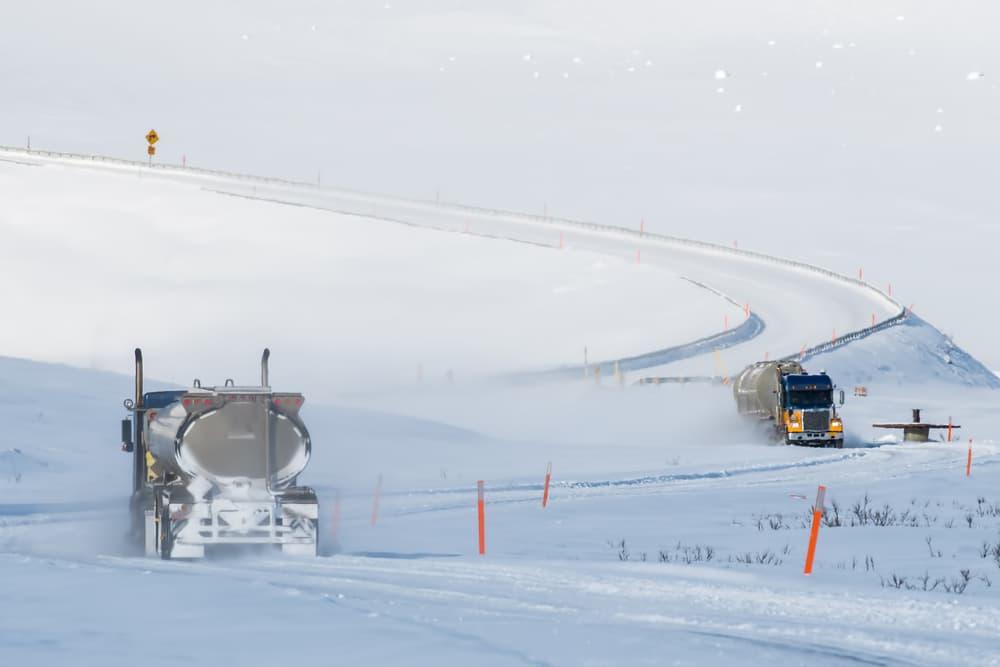 two semis driving through antigun pass on the dalton highway in the snow