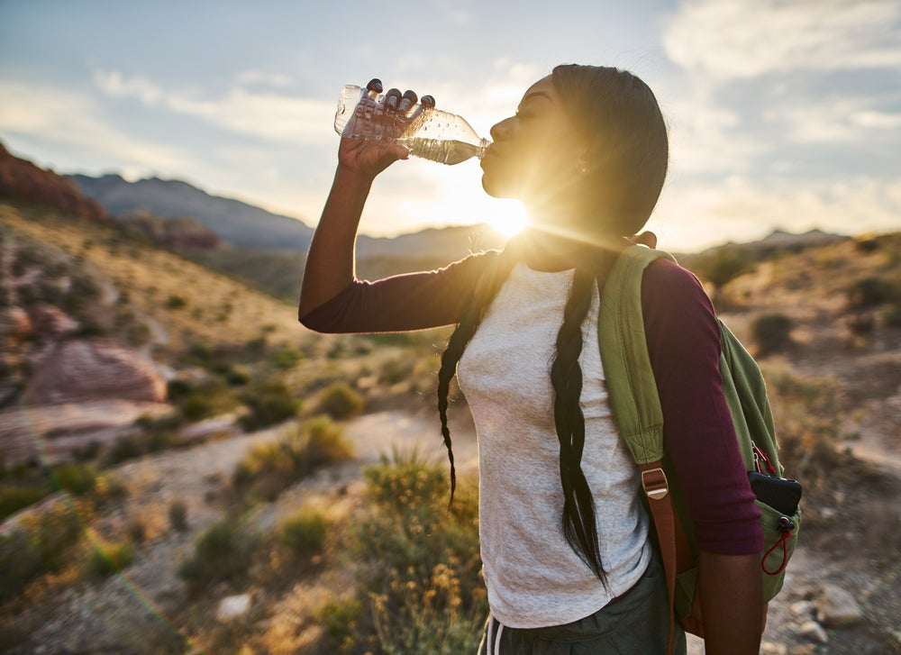Photo of woman drinking water in the desert