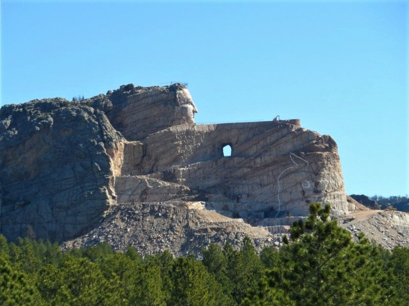 looking over trees towards the construction of the Crazy Horse Memorial