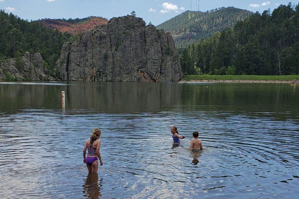 children swim in legion lake near large rock wall