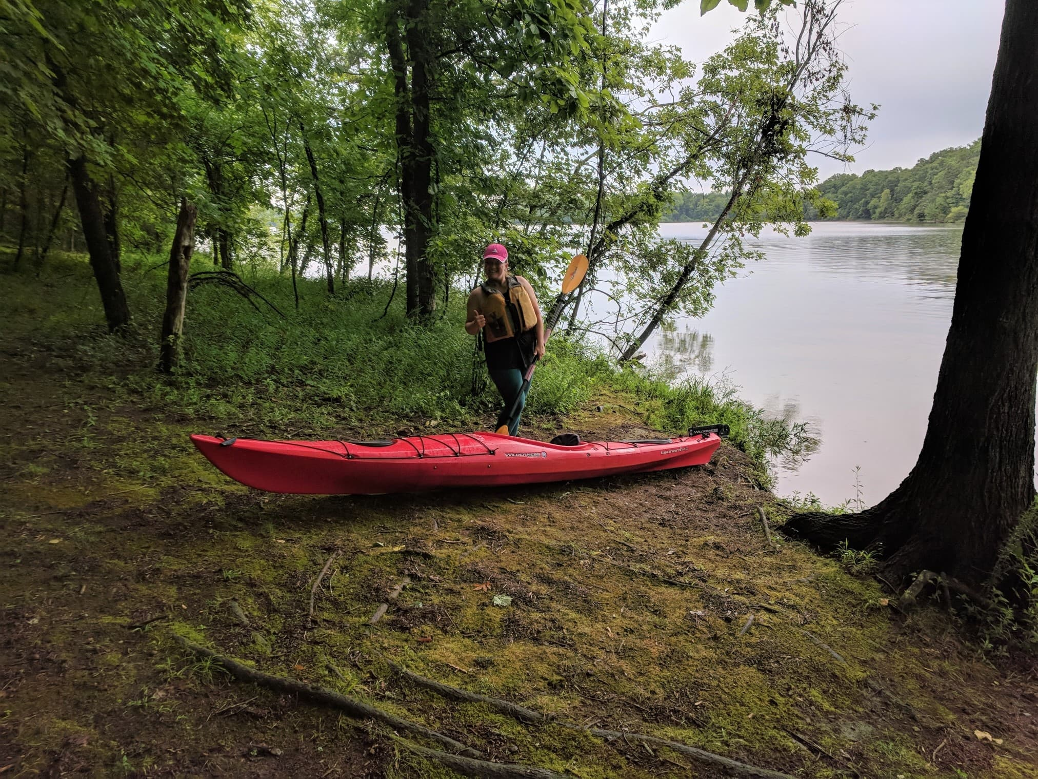 woman standing next to red kayak on shore of lake