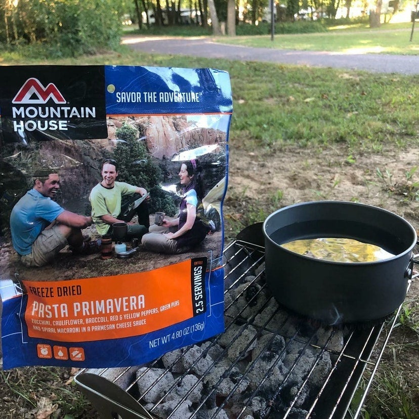 pouch of freeze-dried food near a boiling pot at campsite