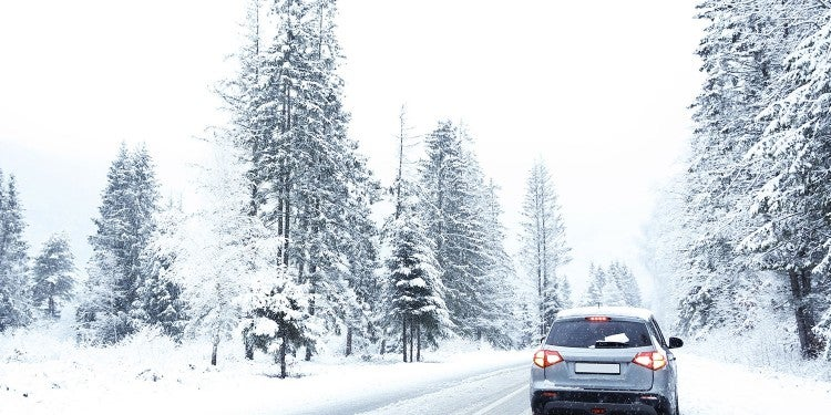 silver SUV on a snowy road for a winter road trip