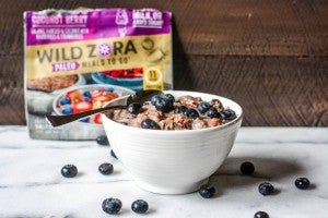 spoon with white bowl filled with oatmeal and blueberries with package of Wild Zora freeze dried meal in the background