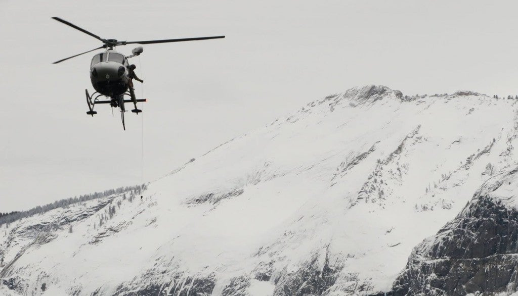 A helicopter involved in a yosemite search and rescue missions flies above snowy mountains in yosemite national park