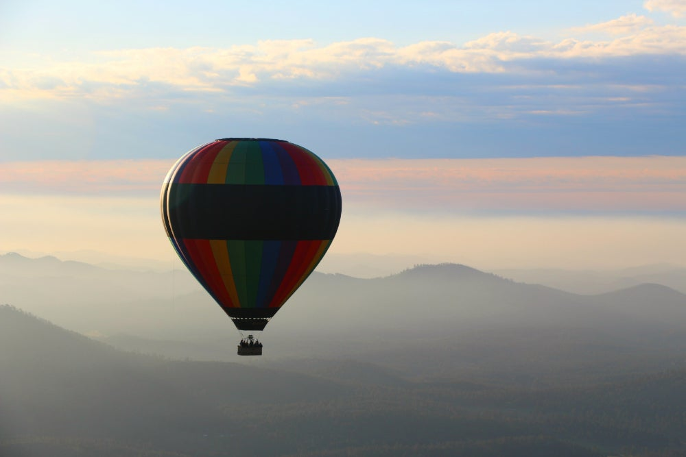 A hot air balloon suspended in mid air with hazy mountains in the background
