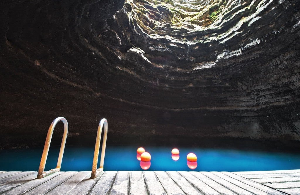 the swimming deck at the bottom of the cavern next to the blue water of homestead crater hot springs near salt lake city