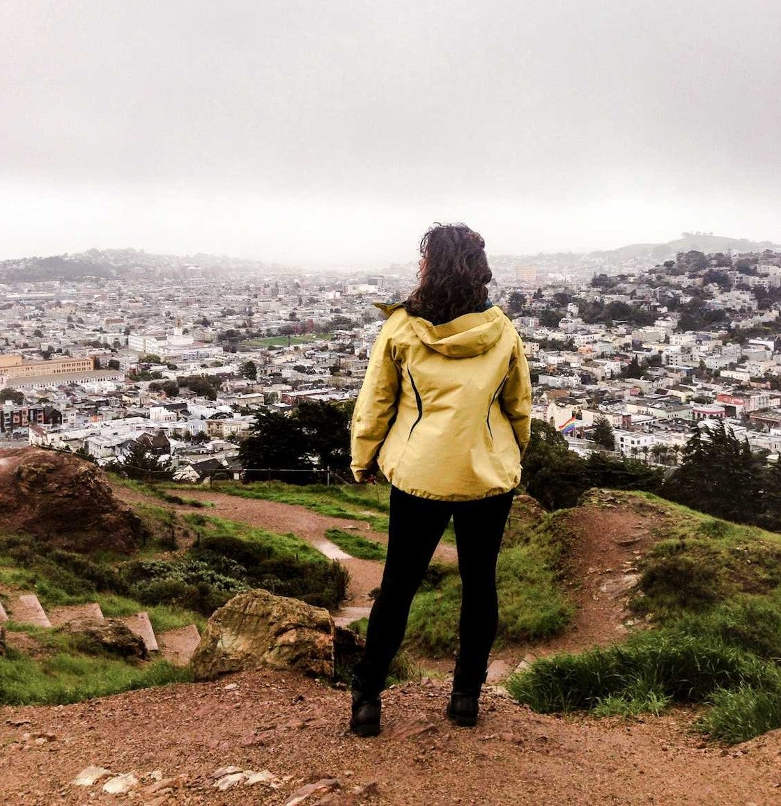 hiker in a yellow jacket overlooks san francisco bay area on a foggy day
