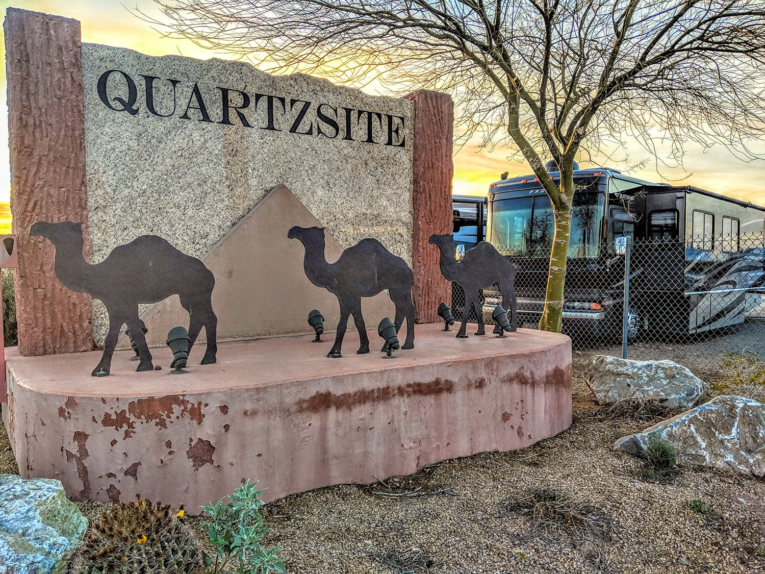 a sign made out of Quartzsite in arizona featuring three metal camels near a pyramid with the name of the town on it, next to a line of RV campers