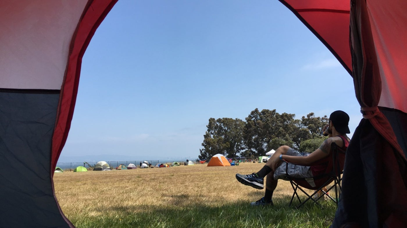 man in camp chair overlooking group tent site is visible from inside red tent