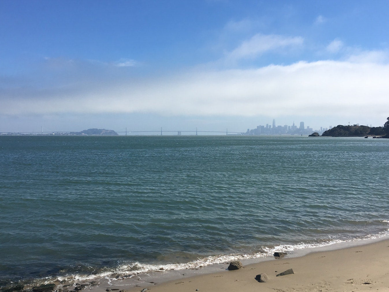 view of san francisco skyline and golden gate bridge from beach shore on angel island
