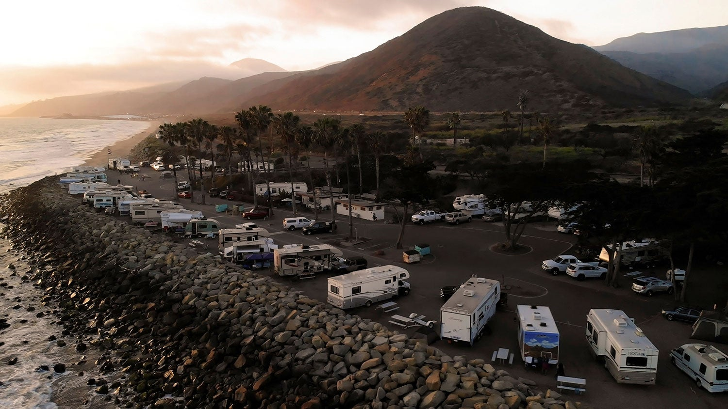 RVs in line in front of a mountain near a coast while beach camping in california