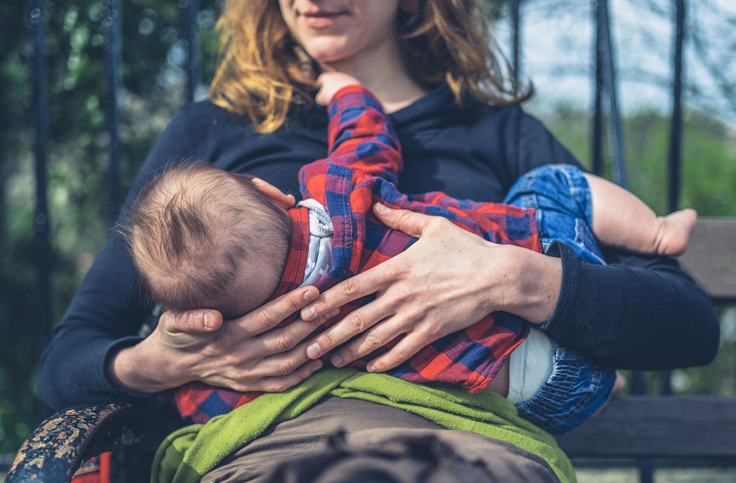 a woman holding a newborn baby and breastfeeding them in the outdoors