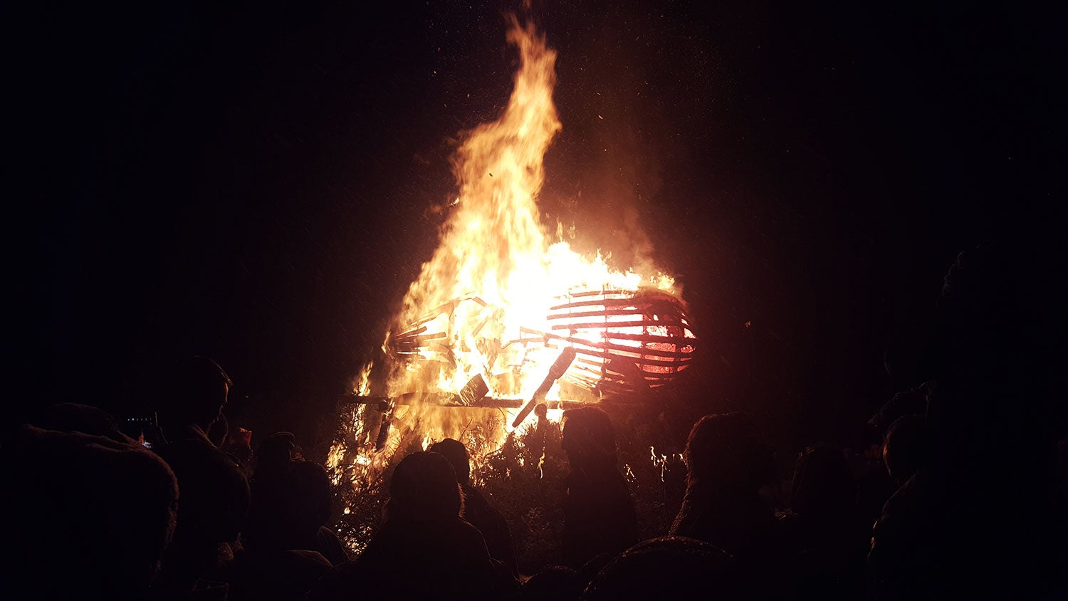 a wooden beetle burning at night around a crowd