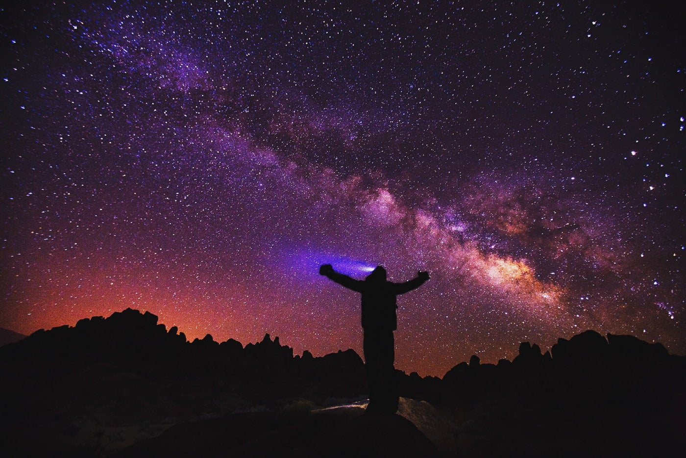 a silhouette of person with arms raised and a headlight beam shining on a silhouetted landscape of rocky hills and a purple night sky filled with stars.