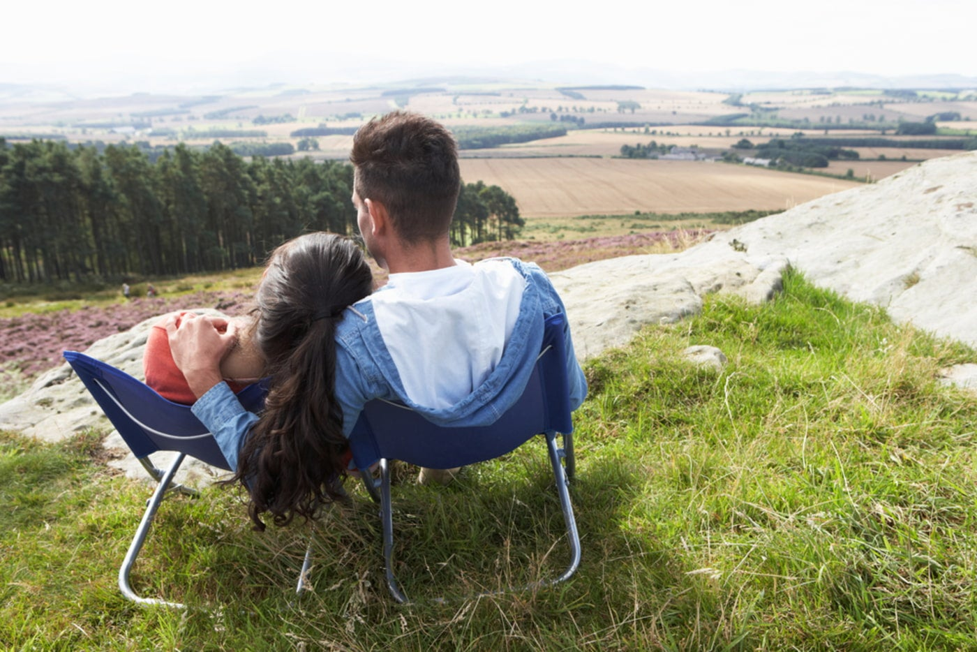 a couple sharing a blue loveseat camp chair, perched on a grassy hill and looking over an agricultural landscape.